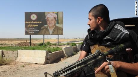 A Peshmerga fighter looks at a billboard of Kurdistan Regional President Masoud Barzani.