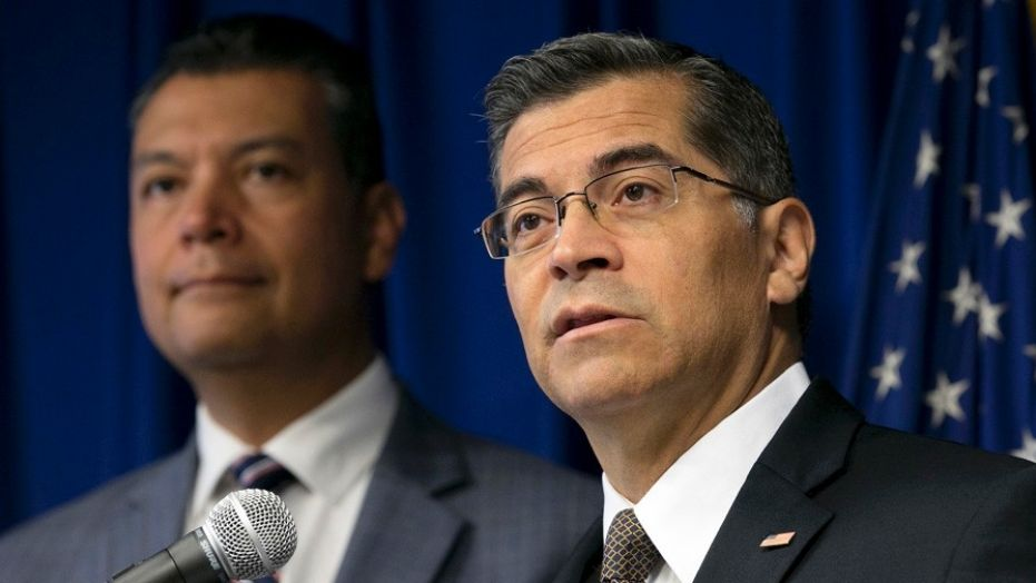 In this Sept. 5, 2017 file photo, California Attorney General Xavier Becerra, right, flanked by Secretary of State Alex Padilla, speaks to reporters at the Capitol in Sacramento.