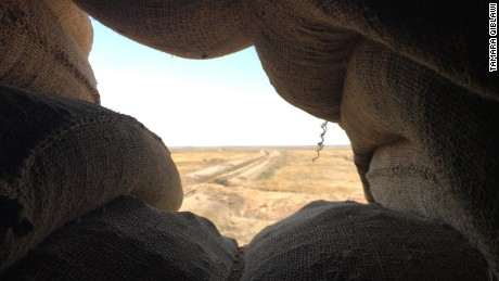 The view from a sandbag sentry position looks out at ISIS territory in the distance.
