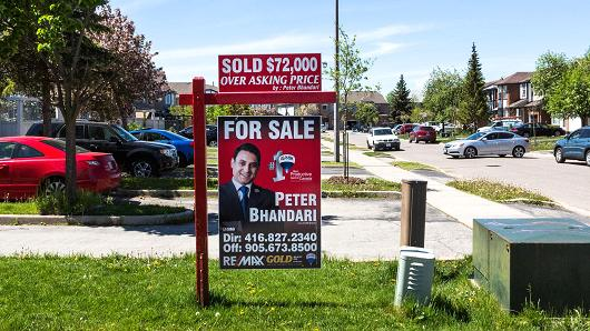 A 'Sold Over Asking' sign is displayed outside of a house in Brampton, Ontario, Canada.