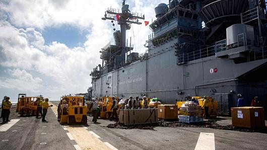 In this U.S. Navy handout, sailors aboard the amphibious assault ship USS Kearsarge (LHD 3) move move pallets of supplies on the flight deck during a replenishment-at-sea with the fast combat support ship USNS Supply (T-AOE 6) for continuing operations in Puerto Rico on September 28, 2017. Kearsarge is assisting with relief efforts in the aftermath of Hurricane Maria.
