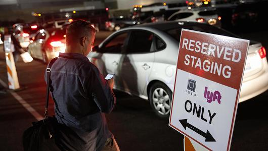 An attendee at the Consumer Electronics Show in Las Vegas on Jan. 6, 2016, waits for a ride in the Uber and Lyft reserved staging area.