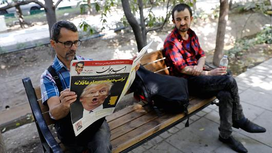 Tehran, October 14, 2017: An Iranian man reads a copy of the daily newspaper 'Omid Javan' bearing a picture of U.S. President Donald Trump with a headline that reads 'Crazy Trump and logical JCPOA' (Joint Comprehensive Plan of Action)