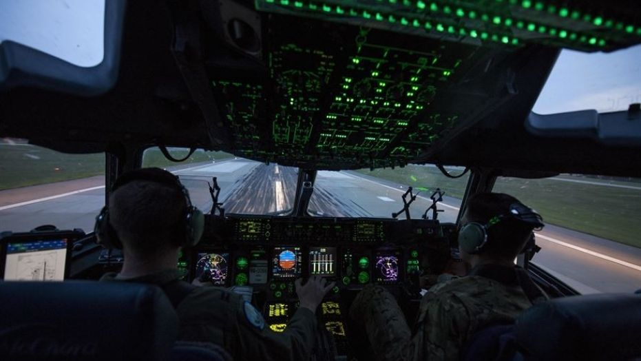 Capts. Wes Sloat (left) and Jared Barkemeger, 7th Airlift Squadron pilots, operate a C-17 Globemaster III during takeoff from the flight line of Fort Bragg, N.C., during Operation Panther Storm, July 27, 2017.