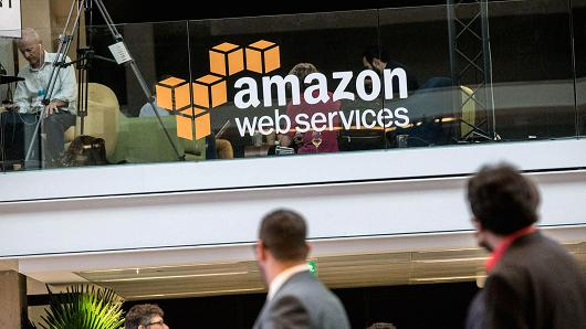 Attendees stand near Amazon.com Web Services signage during the Station F startup campus launch party in Paris, France, on Thursday, June 29, 2017.