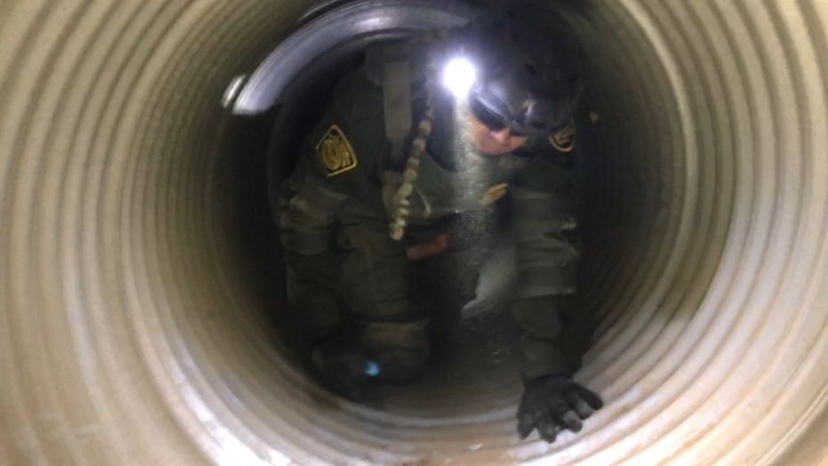 A Border Patrol agent takes part in a training exercise inside a drain.