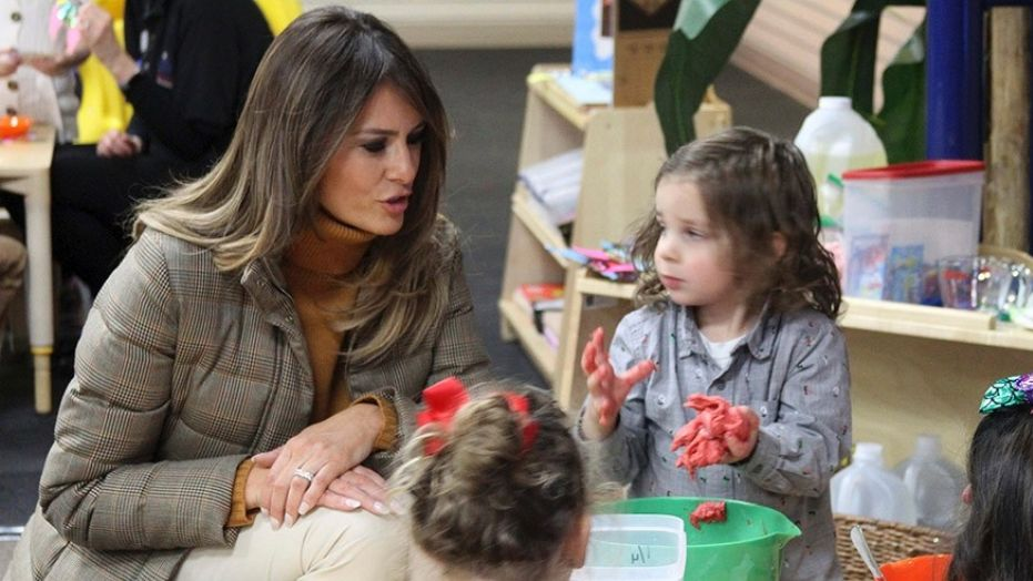 First lady Melania Trump watches as children form objects from Play-Doh at Joint Base Elmendorf-Richardson, Alaska.