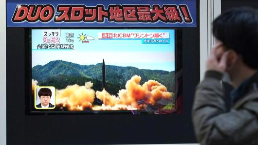 A pedestrian walks in front of a television screen displaying file news footage of a North Korean missile launch, in Tokyo on November 29, 2017