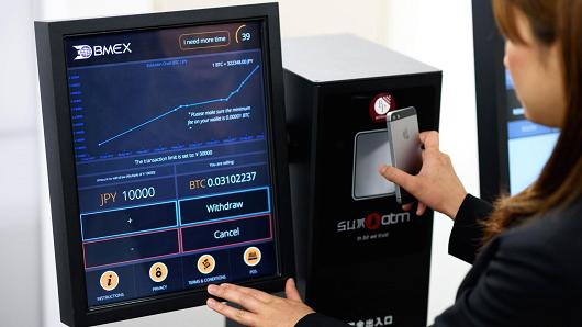 An employee demonstrates the usage of a bitcoin automated teller machine (ATM) at the BITPoint Japan Co. headquarters in Tokyo.