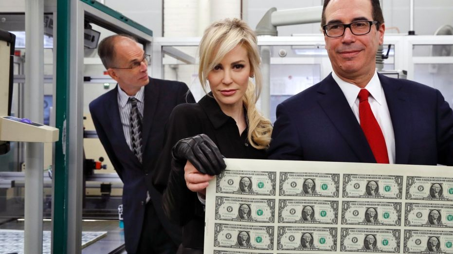 Treasury Secretary Steven Mnuchin, right, and his wife Louise Linton, hold up a sheet of new $1 bills, the first currency notes bearing his and U.S. Treasurer Jovita Carranza's signatures Wednesday.
