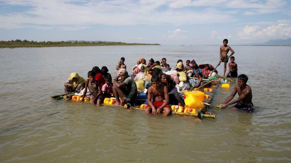 Rohingya refugees sail towards the bank of Naf River on a makeshift raft after crossing the Bangladesh-Burma border, at Sabrang in Teknaf, near Cox's Bazar, Bangladesh, November 11, 2017.