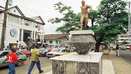 Monrovian pedestrians on Broad Street look up at a statue of George Weah, arguably Liberia's most famous son.