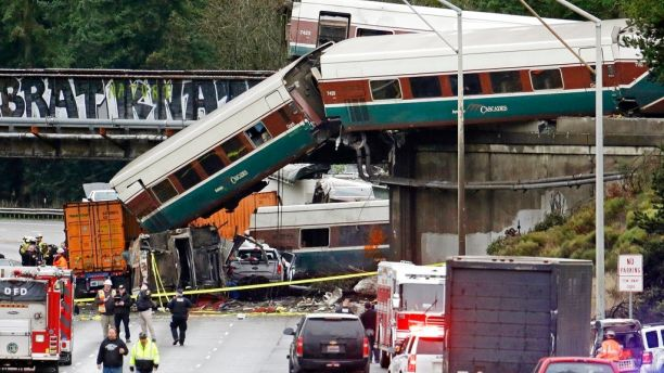 FILE - In this Dec. 18, 2017 file photo, cars from an Amtrak train lay spilled onto Interstate 5 below alongside smashed vehicles as some train cars remain on the tracks above in DuPont, Wash. Dozens of 911 call recordings released by South Sound 911 Dispatch provide a vivid account of the Dec. 18 wreck from survivors and witnesses. Authorities say it could take more than a year to understand how the train carrying 85 passengers and crew members could have ended in disaster as it made its inaugural run along a fast, new 15-mile (24-kilometer) bypass route. (AP Photo/Elaine Thompson, file)
