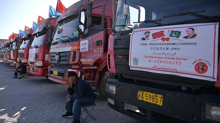 A Chinese worker sits near trucks carrying goods during the opening of a trade project in Gwadar Port, Pakistan, on November 13, 2016.