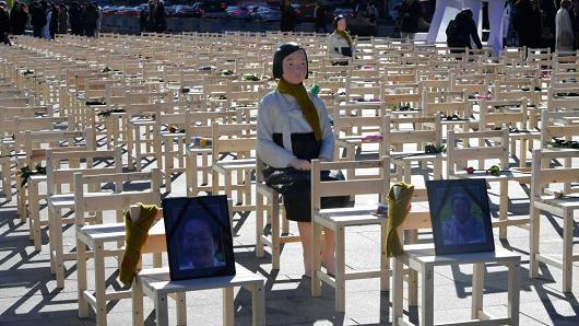 A statue of a 'comfort woman' is displayed in an installation of empty chairs set up in central Seoul to commemorate the death of eight former sex slaves.