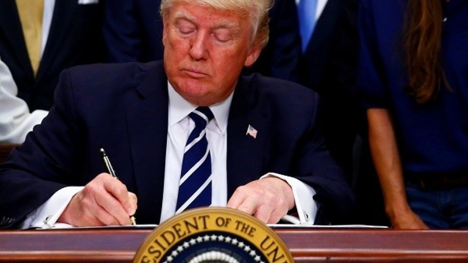 President Donald Trump signs an executive order at the White House, June 15, 2017.