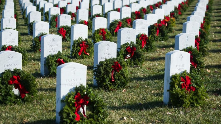 Wreaths rest against headstones at Arlington National Cemetery as Wreaths Across America places remembrance wreaths on headstones at the cemetery in Arlington, Va., Saturday, Dec. 16, 2017.