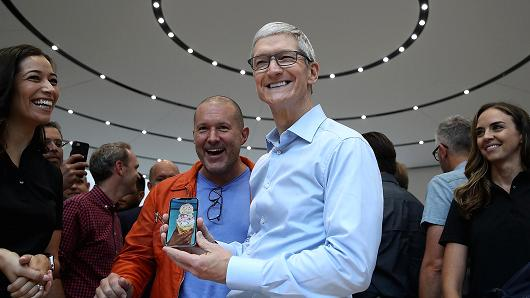 Apple CEO Tim Cook (R) and Apple chief design officer Jonathan Ive (L) look at the new Apple iPhone X during an Apple special event at the Steve Jobs Theatre on the Apple Park campus on September 12, 2017 in Cupertino, California.