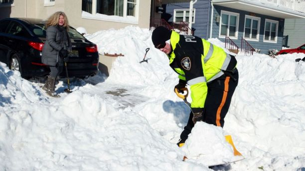 Longport Police Officer Gabe Guerrieri helps Sarah Mammucari with shoveling her driveway, Friday, Jan. 5, 2018, in Longport, N.J. (Edward Lea/The Press of Atlantic City via AP)
