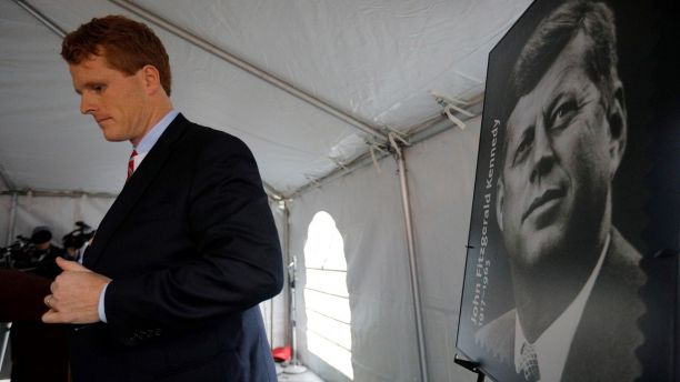 U.S. Congressman Joe Kennedy III stands next to a poster of a stamp of featuring his great-uncle, U.S. President John F. Kennedy, during ceremonies on the 100th anniversary of the birth of President Kennedy outside the home where he was born in Brookline, Massachusetts, U.S., May 29, 2017.   REUTERS/Brian Snyder - RC1B120E0090