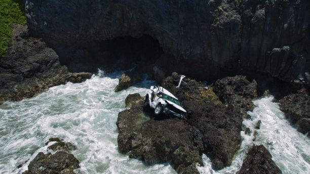 In this May 30, 2016 photo provided by Tom Johnson, a vehicle sits at the bottom of a cliff off Maui's Hana Highway in Hana, Hawaii. Alexandria Duval, who is also known as Alison Dadow, was driving the vehicle when it plunged off the Maui cliff May 29, and is charged with second-degree murder in the death of her twin, Anastasia Duval, also known as Ann Dadow, who was in the passenger's seat. (Tom Johnson via AP) MANDATORY CREDIT