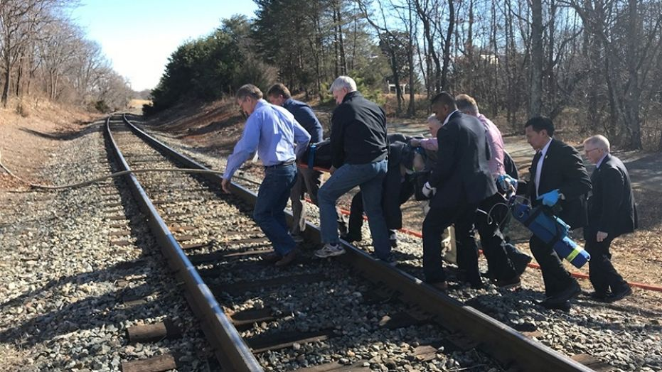 Ohio Rep. Brad Wenstrup, Arizona Sen. Jeff Flake and Louisiana Sen. Bill Cassidy of Louisiana – in the front -- were part of a group carrying an injured person to safety after Wednesday's train wreck.