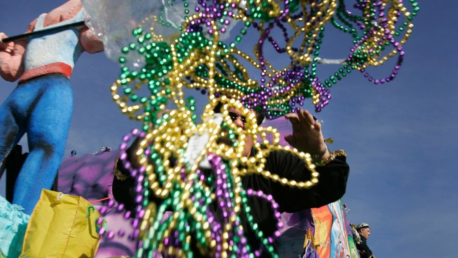 File - A parade rider throws out handfuls of beads during a Mardi Gras parade.