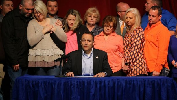 The parents of the deceased 15 year old Bailey Holt, left, stand in tears as Kentucky Gov. Matt Bevin signs the prayer proclamation on Friday, Jan. 26, 2018 in Benton, Ky.  Marshall County High School reopened its doors Friday as the school day began with an assembly. Police say two students were killed, 14 were wounded by gunfire and seven others suffered other injuries when the boy opened fire at the school Tuesday before classes began. (AP Photo/Robert Ray)