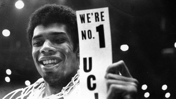 FILE - In this March 23, 1968, file photo, UCLA's Lew Alcindor, with the basket netting draped over his shoulders, holds a sign just after leading UCLA to the NCAA basketball championship in Los Angeles on March 23, 1968.  Muhammad Ali's actions influenced others. Alcindor boycotted the 1968 Summer Olympics. boycotted the 1968 Summer Olympics. After winning his first NBA championship in 1971, he took the Muslim name Kareem Abdul-Jabbar. (AP Photo/File)