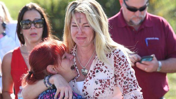 Dos mujeres lloran tras el reporte de un tiroteo en la Escuela Secundaria Marjory Stoneman Douglas de Parkland, Florida, el miércoles 14 de febrero de 2018. (AP Foto/Joel Auerbach)