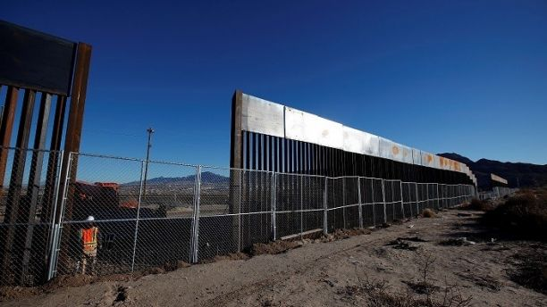 A worker stands next to a newly built section of the U.S.-Mexico border fence at Sunland Park, U.S. opposite the Mexican border city of Ciudad Juarez, Mexico January 25, 2017. Picture taken from the Mexico side of the U.S.-Mexico border. REUTERS/Jose Luis Gonzalez - RC1E79E73750