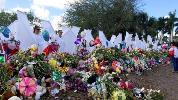 "Seventeen people dressed as angels stand Sunday, Feb. 25, 2018, at the memorial outside Marjory Stoneman Douglas High School in Parkland, Fla., for those killed in a shooting on Feb. 14. Organizer Terry Decarlo said the idea originated after the death of University of Wyoming student Matthew Shepard, who was tortured and murdered in 1998. Decarlo said the costumes now travel to disasters and mass shootings around the country. ""We want to the survivors to know angels are looking over them and protecting them,"" Decarlo said. (AP Photo/Terry Spencer)"