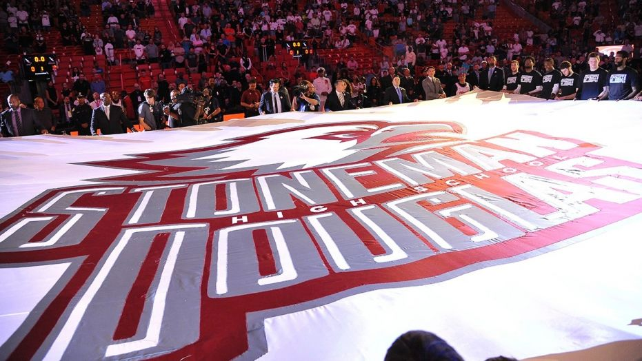 A large banner in memory of the victims of the Marjory Stoneman Douglas High School shooting is unfurled before an NBA basketball game in Miami on Saturday, Feb. 24, 2018.