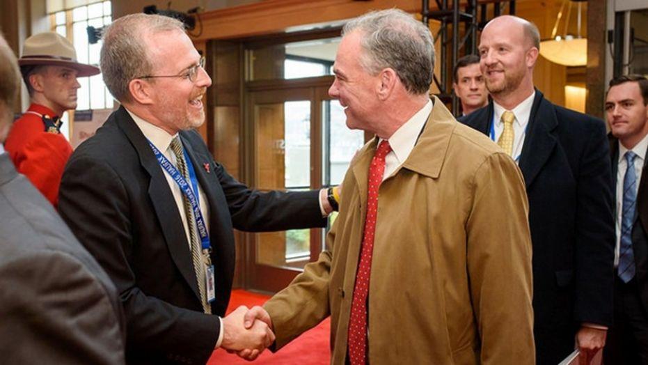 David Kramer greets Sen. Tim Kaine at the Halifax International Security Forum in November 2016.