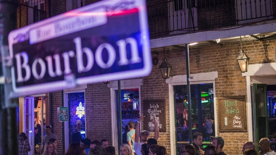 Revelers walk down Bourbon Street, located in the French Quarter of New Orleans, La., July 11, 2015.