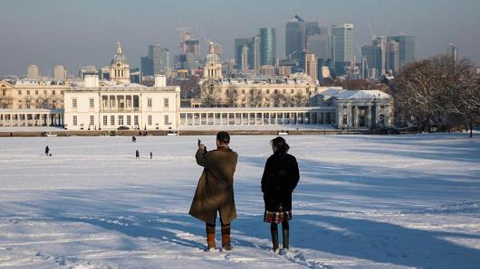 People stop and take a picture in a snow-covered Greenwich Park on February 28, 2018 in London, United Kingdom