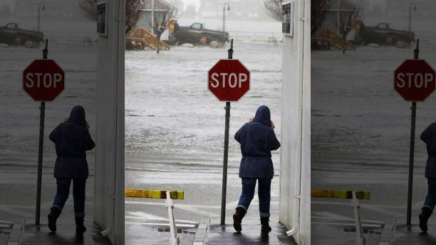 A passerby looks on as water from Scituate Harbor floods streets, in Scituate, Mass., Friday, March 2, 2018. A major nor'easter pounded the East Coast on Friday, packing heavy rain and strong winds as residents from the mid-Atlantic to Maine braced for coastal flooding. (AP Photo/Steven Senne)
