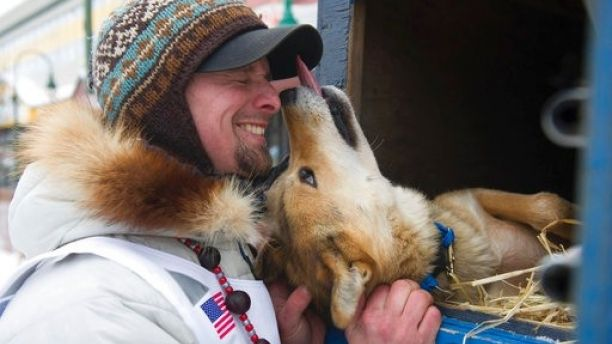 Rookie musher Matt Failor, of Willow, Alaska, gets friendly with Pantera, a female dog in his team, prior to the ceremonial start of the Iditarod Trail Sled Dog Race, Saturday, March 3, 2018, in Anchorage, Alaska. (AP Photo/Michael Dinneen)