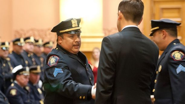 In this 2014 photo, Jersey City Police Sgt. Christopher Robateau, left, hands with Mayor Steve Fulop when he was promoted to lieutenant with the Jersey City Police Department in 2014. Robateau, 49, was killed on the New Jersey Turnpike, Friday morning, Jan. 5, 2018. As he exited his car to help a motorist on his way to work, Robateau was struck by a vehicle. (Reena Rose Sibayan/The Jersey Journal via AP)