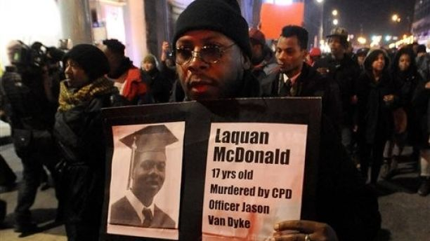 FILE - In this Tuesday, Nov. 24, 2015, file photo, a protester holds a sign as people rally for 17-year-old Laquan McDonald, who was shot 16 times by Chicago Police Department Officer Jason Van Dyke in Chicago. McDonald, whose name demonstrators are shouting as they march the streets and plan to shut down the city's glitziest shopping corridor on Friday, lived a troubled life full of disadvantages and at least one previous brush with the law. (AP Photo/Paul Beaty, File)