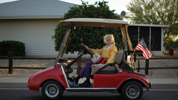 A woman rides in a golf cart with her dog in Sun City, Arizona, January 6, 2013. Sun City was built in 1959 by entrepreneur Del Webb as America?s first active retirement community for the over-55's. Del Webb predicted that retirees would flock to a community where they were given more than just a house with a rocking chair in which to sit and wait to die. Today?s residents keep their minds and bodies active by socializing at over 120 clubs with activities such as square dancing, ceramics, roller skating, computers, cheerleading, racquetball and yoga. There are 38,500 residents in the community with an average age 72.4 years.    Picture taken January 6, 2013.  REUTERS/Lucy Nicholson (UNITED STATES - Tags: SOCIETY)  ATTENTION EDITORS - PICTURE 16 OF 30 FOR PACKAGE 'THE SPORTY SENIORS OF SUN CITY' SEARCH 'SUN CITY' FOR ALL IMAGES - LM2E91F0XAN01