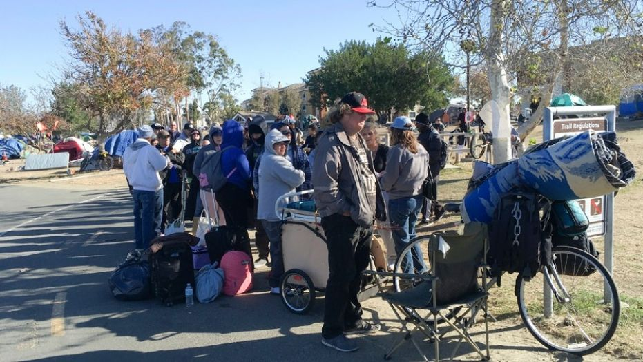 Homeless people line up in preparation to move from their homeless camp site along a riverbed in Anaheim, Calif., Feb. 20, 2018.