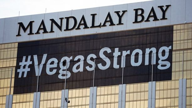 FILE - In this Oct. 16, 2017, file photo, workers install a #VegasStrong banner on the Mandalay Bay hotel and casino in Las Vegas. The official slogan of Las Vegas,
